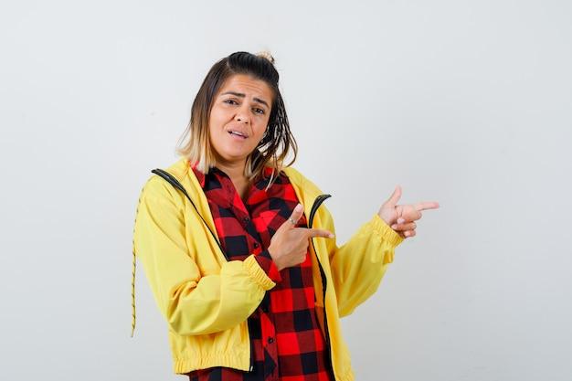 Portret van een mooie vrouw die recht in shirt, jas wijst en verward vooraanzicht kijkt