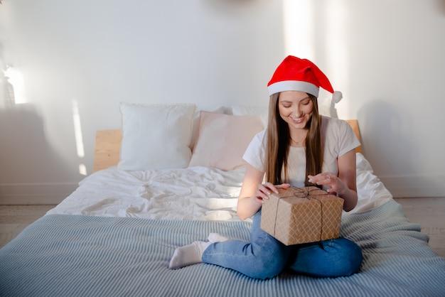 Portret van een mooie vrouw die santahoed het glimlachen draagt. vrouw met presenteert horizontale weergave presenteert en viering concept.