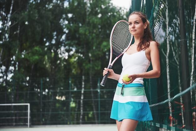 Portret van een mooie vrouw die tennis beoefent.
