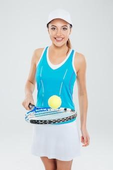 Portret van een mooie vrouw die tennis speelt en naar de camera kijkt