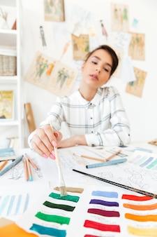 Portret van een mooie vrouw die van de manierontwerper op workshop werkt