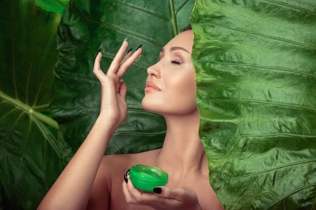 Portret van een mooie vrouw die vochtinbrengende gel op haar huid toepast.