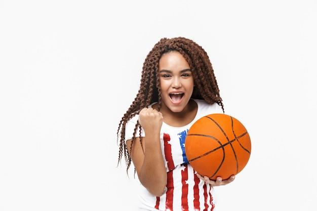 Portret van een mooie vrouw die zich verheugt en basketbal vasthoudt tijdens het spel terwijl ze geïsoleerd tegen een witte muur staat
