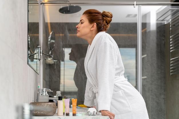Portret van een mooie vrouw die zichzelf in de spiegel controleert