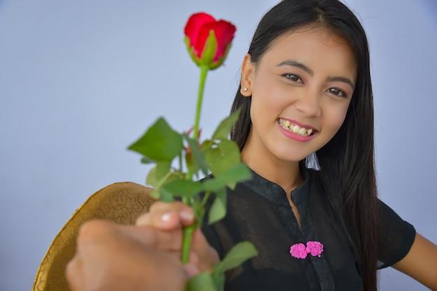 Portret van een mooie vrouw, een birmese mooie vrouw met een rode roos in haar hand op valentijnsdag.