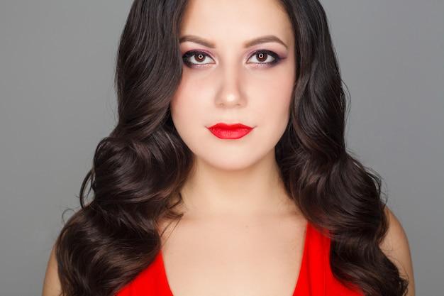 Portret van een mooie vrouw, een brunette model met make-up op een grijs