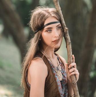 Portret van een mooie vrouw hippies in een bos. het concept van eenheid met de natuur