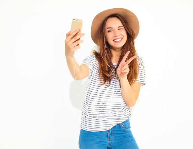 Portret van een mooie vrouw in de zomer hipster kleren die een selfie nemen op witte muur wordt geïsoleerd. knipogen en vredesteken tonen