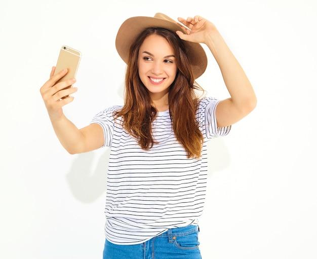 Portret van een mooie vrouw in de zomer hipster kleren die een selfie nemen op witte muur wordt geïsoleerd