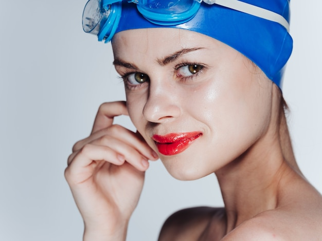 Portret van een mooie vrouw in een blauwe badmuts en glazen