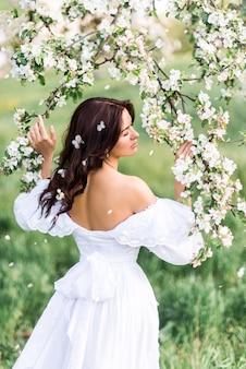 Portret van een mooie vrouw in een bloeiende tuin. een meisje in een lentetuin. foto van de achterkant ..
