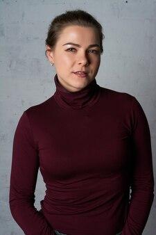 Portret van een mooie vrouw in een rode coltrui in de buurt van een witte bakstenen muur.