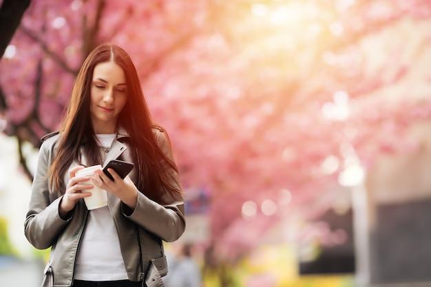 Portret van een mooie vrouw in een sakuraboompark en babbelend op de telefoon