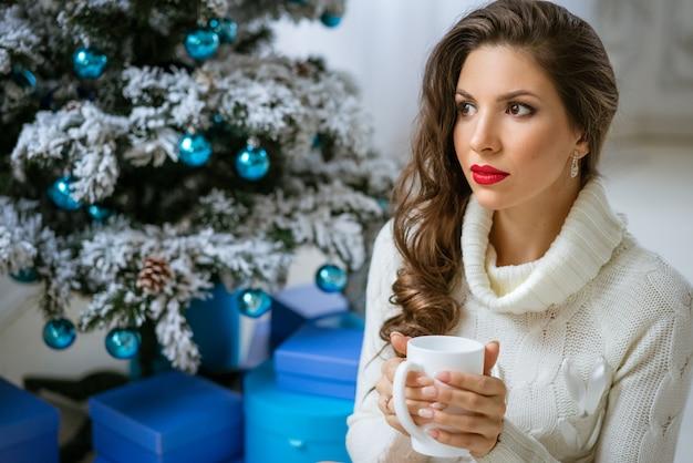 Portret van een mooie vrouw in een trui met een mok