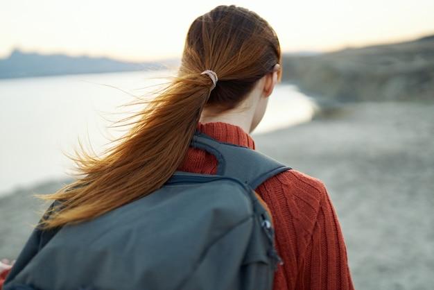 Portret van een mooie vrouw in een trui met een rugzak reizen toerisme bergen zee