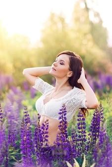 Portret van een mooie vrouw in een veld met paarse bloemen. zomer zonnige foto met een jong donkerbruin meisje in paarse lupines