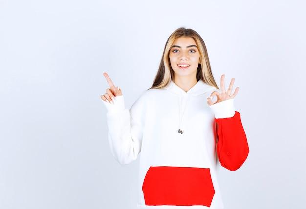 Portret van een mooie vrouw in een warme hoodie die omhoog wijst en een goed gebaar toont