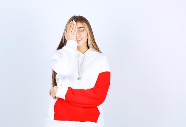 Portret van een mooie vrouw in een warme hoodie die staat en één oog bedekt met de hand