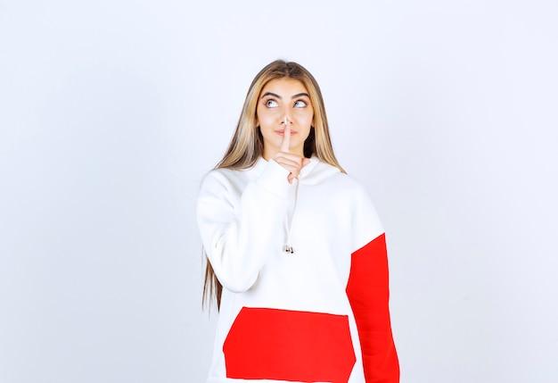 Portret van een mooie vrouw in een warme hoodie die staat en een stil teken doet