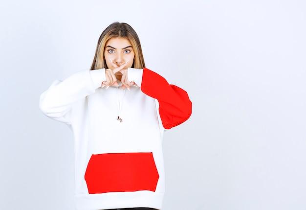 Portret van een mooie vrouw in een warme hoodie die staat en gekruiste vingers laat zien