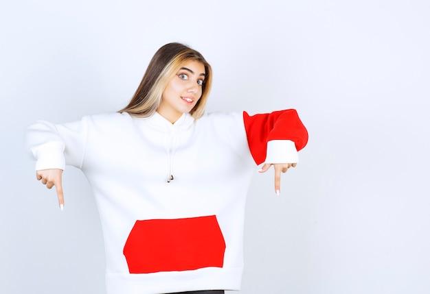 Portret van een mooie vrouw in een warme hoodie die staat en naar beneden wijst