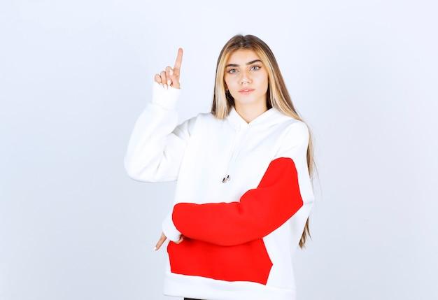 Portret van een mooie vrouw in een warme hoodie die staat en naar boven wijst