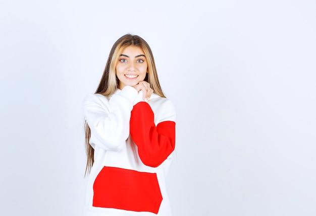 Portret van een mooie vrouw in een warme hoodie die staat en naar de camera kijkt