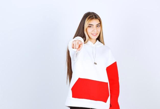 Portret van een mooie vrouw in een warme hoodie die staat en naar de camera wijst