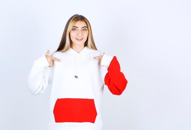 Portret van een mooie vrouw in een warme hoodie die staat en naar zichzelf wijst