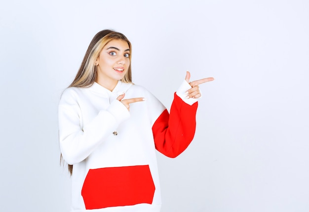Portret van een mooie vrouw in een warme hoodie die staat en wegwijst