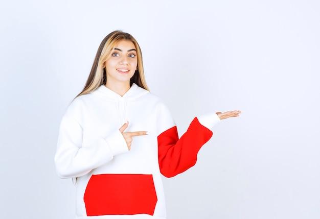 Portret van een mooie vrouw in een warme hoodie die staat en wijst naar de geopende handpalm