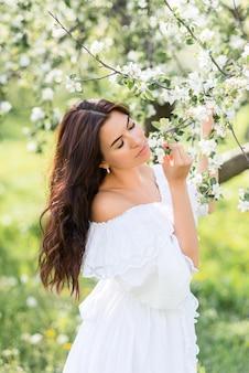 Portret van een mooie vrouw in een witte jurk in een lentetuin. een meisje met haar ogen dicht ademt de geur van bloeiende bomen in.