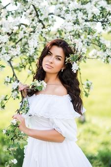Portret van een mooie vrouw in een witte jurk in een lentetuin. een meisje tussen de bloeiende bomen.