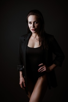 Portret van een mooie vrouw in een zwarte romper en jas poseren op een donkere achtergrond