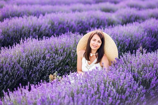 Portret van een mooie vrouw in lavendel. een meisje in een witte zomerjurk en hoed in de zomer in de natuur.