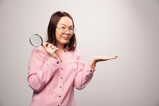 Portret van een mooie vrouw in roze kleding die een vergrootglas vasthoudt. hoge kwaliteit foto