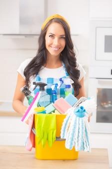 Portret van een mooie vrouw in schort klaar om de keuken schoon te maken, met verschillende schoonmaakspullen op een tafel voor haar.