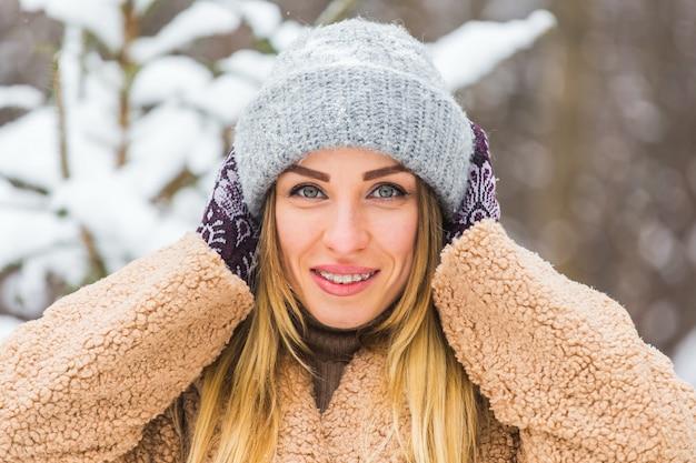Portret van een mooie vrouw met beugels aan de tanden. glimlachend meisje met beugels. gelukkig lachende vrouw met accolades in de winter natuur. tandheelkundige gezondheid concept.