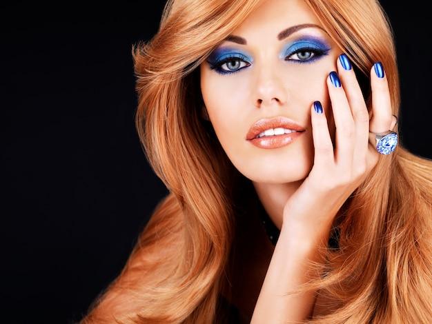 Portret van een mooie vrouw met blauwe nagels, blauwe make-up en lange rode haren op zwarte muur