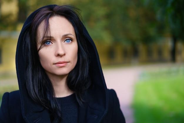 Portret van een mooie vrouw met blauwe ogen in een zwarte jas op straat