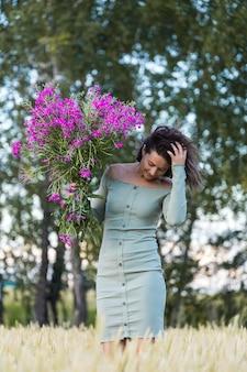 Portret van een mooie vrouw met een boeket bloemen wandelen in de velden