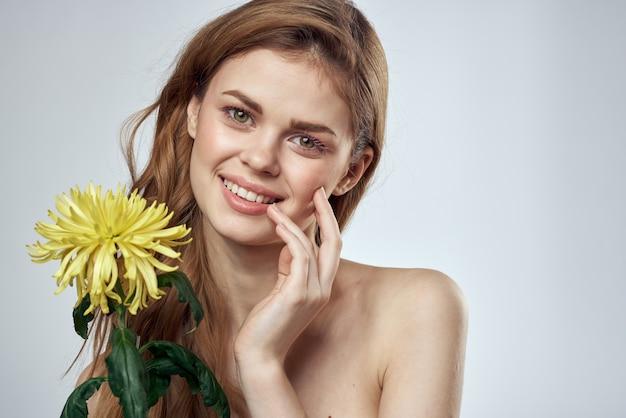 Portret van een mooie vrouw met een gele bloem op een licht bijgesneden met model
