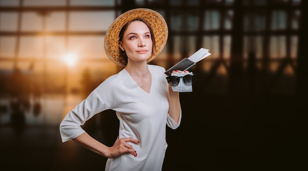 Portret van een mooie vrouw met een gele hoed die op de luchthaven staat met een paspoort en ticket. reisconcept. gemengde media