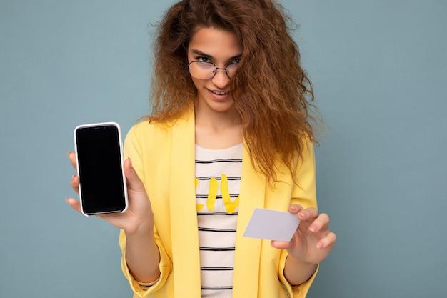 Portret van een mooie vrouw met een gele jas en een optische bril die op een achtergrondmuur is geïsoleerd en een telefoon toont met een leeg scherm en een creditcard die naar de camera kijkt. uitknippen