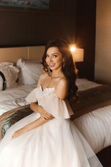 Portret van een mooie vrouw met een huwelijkskapsel en dure juwelen met diamanten. brunette model meisje met bruids make-up en luxe oorbellen