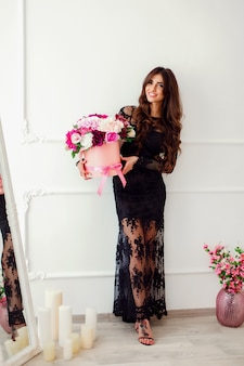 Portret van een mooie vrouw met een mand met bloemen