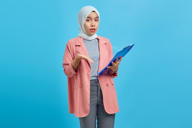 Portret van een mooie vrouw met een map met een verbaasd gezicht op een blauwe achtergrond