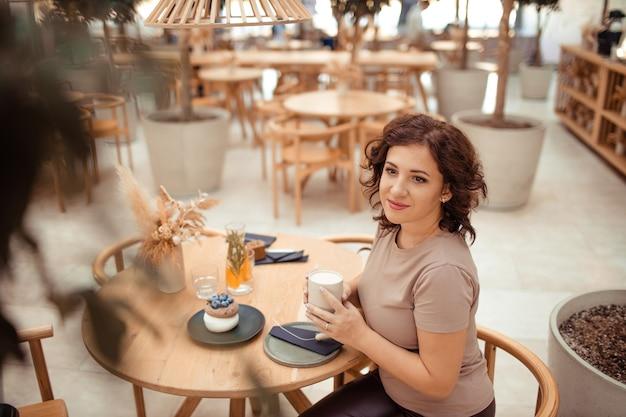 Portret van een mooie vrouw met een mok koffie in haar handen in een stadscafé