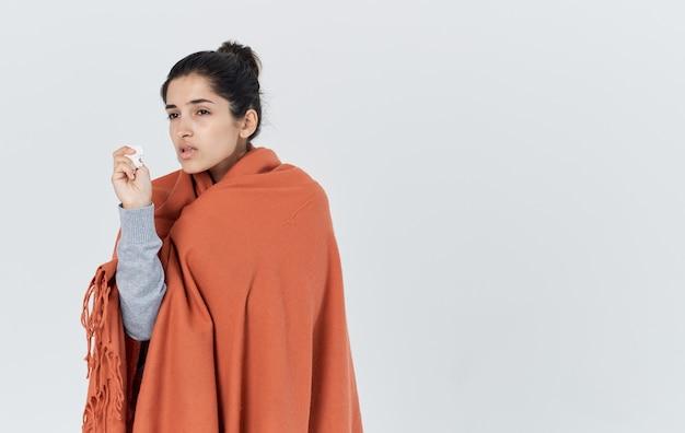 Portret van een mooie vrouw met een oranje plaid op haar schouders allergie voor gezondheidsproblemen