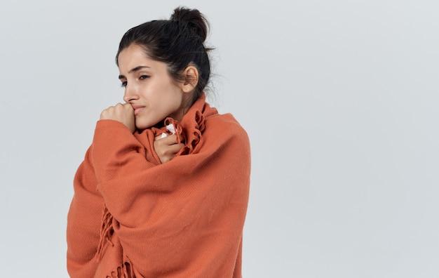 Portret van een mooie vrouw met een oranje plaid op haar schouders gezondheidsproblemen allergie servet. hoge kwaliteit foto